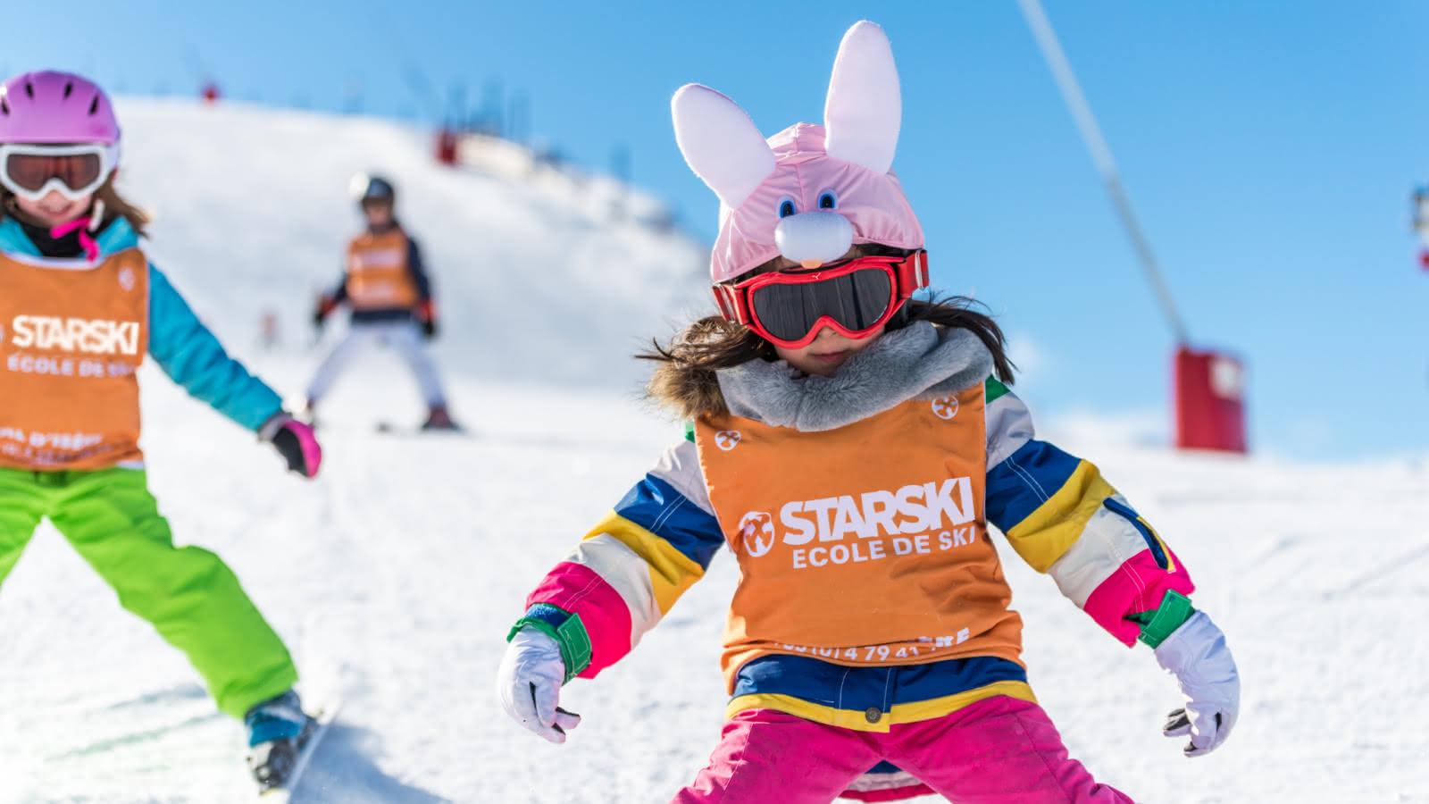 Les enfants apprennent le ski tout en s'amusant.